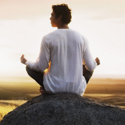 Man meditating on a rock image 250px